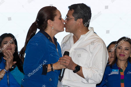Honduran President Juan Orlando Hernandez kisses his wife Ana Garcia during a rally with supporters on election night, in Tegucigalpa, Honduras, . Hernandez, a conservative U.S. ally, appeared likely to win a second term despite opposition claims that his re-election is an unconstitutional power grab