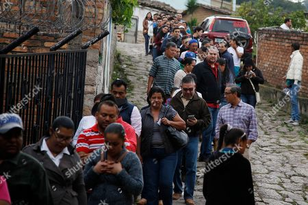 People stand in line outside a polling station during the general elections in Santa Lucia, Honduras, . Honduran President Juan Orlando Hernandez, a conservative U.S. ally, tries to win a second term on Sunday despite opposition claims that his re-election is an unconstitutional power grab