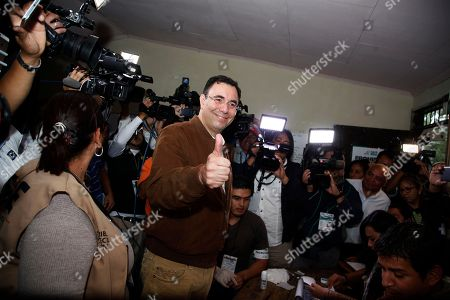 Liberal Party presidential candidate Luis Zelaya poses for photos as he receives his ballot at a polling station during the general elections in Santa Lucia, Honduras, . Honduran President Juan Orlando Hernandez, a conservative U.S. ally, tries to win a second term on Sunday despite opposition claims that his re-election is an unconstitutional power grab