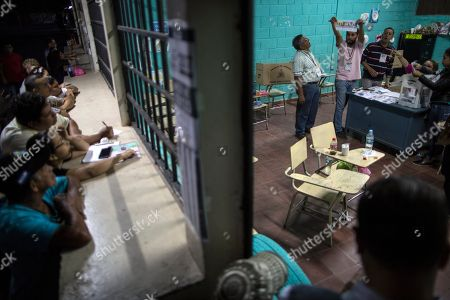 An electoral worker shows a ballot during the vote count in the general elections, in Tegucigalpa, Honduras, . Honduran President Juan Orlando Hernandez, a conservative U.S. ally, appeared likely to win a second term despite opposition claims that his re-election is an unconstitutional power grab