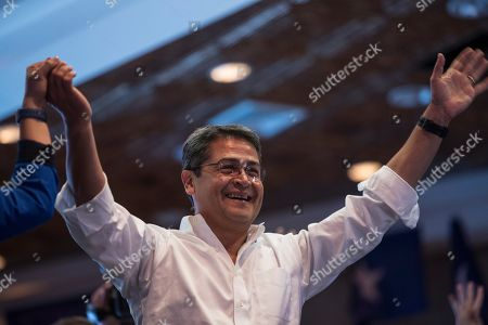 Honduran President Juan Orlando Hernandez greets supporters during a meeting with supporters on election night, in Tegucigalpa, Honduras, . Hernandez, a conservative U.S. ally, appeared likely to win a second term despite opposition claims that his re-election is an unconstitutional power grab