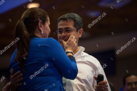 Stock Picture of First Lady Ana Garcia, cleans the mouth of Honduran President Juan Orlando Hernandez after kissing him during an election night rally with supporters, in Tegucigalpa, Honduras, . Hernandez, a conservative U.S. ally, appeared likely to win a second term despite opposition claims that his re-election is an unconstitutional power grab