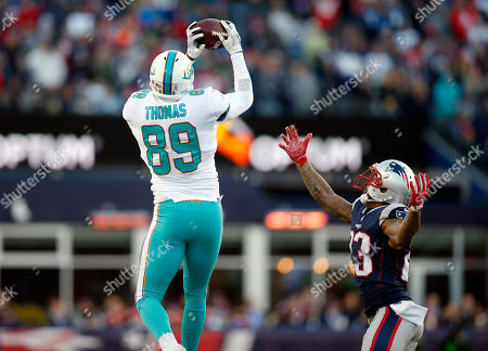 Julius Thomas, Patrick Chung. Miami Dolphins tight end Julius Thomas catches a pass over New England Patriots safety Patrick Chung during the second half of an NFL football game, in Foxborough, Mass