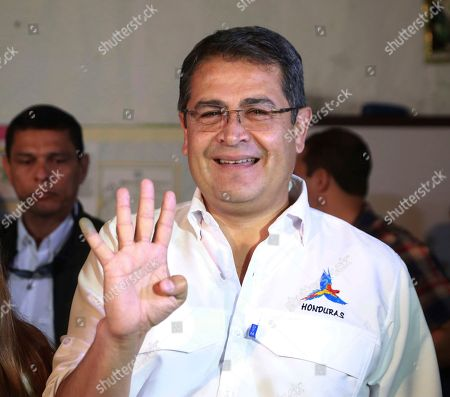 In this photo released by Honduras' Presidency, Honduran President Juan Orlando Hernandez poses for photographers after casting his vote during the general elections in Lempira, Honduras, . Hernandez, a conservative U.S. ally, tries to win a second term on Sunday despite opposition claims that his re-election is an unconstitutional power grab