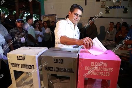 In this photo released by Honduras' Presidency, Honduran President Juan Orlando Hernandez casts his vote during the general elections in Lempira, Honduras, . Hernandez, a conservative U.S. ally, tries to win a second term on Sunday despite opposition claims that his re-election is an unconstitutional power grab