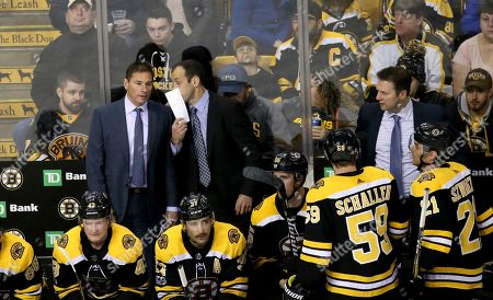 Boston Bruins head coach Bruce Cassidy, left, listens to assistant coach Jay Pandolfo, center, as assistant coach Joe Sacco, right, looks on during the third period of an NHL hockey game against the Edmonton Oilers in Boston