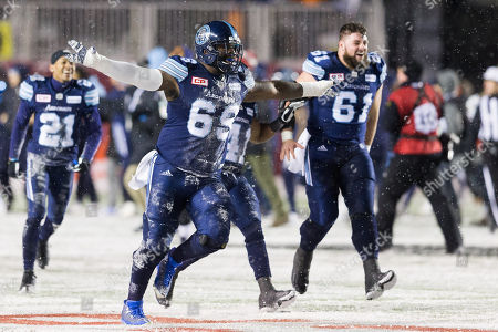 Stock Picture of Toronto Argonauts D.J. Sackey (65) and Sean McEwen (61) celebrate victory after the CFL Grey Cup Championship game between Calgary Stampeders and Toronto Argonauts at TD Place Stadium in Ottawa, Canada. Toronto Argonauts won the Grey Cup by a score of 27-24