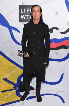 Rick Owens poses in the press room with the Geoffrey Beene lifetime achievement award at the CFDA Fashion Awards at the Hammerstein Ballroom, in New York