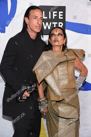 Rick Owens, left, poses in the press room with the Geoffrey Beene lifetime achievement award with Michele Lamy at the CFDA Fashion Awards at the Hammerstein Ballroom, in New York