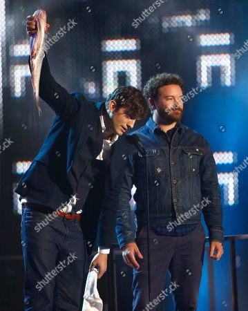 Ashton Kutcher, left, and Danny Masterson present the award for collaborative video of the year at the CMT Music Awards at Music City Center, in Nashville, Tenn. Kutcher is holding up a catfish for good luck in honor of the Nashville Predators hockey team playing in the NHL Stanley Cup final