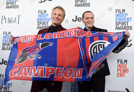 Viggo Mortensen, left, and Matt Ross hold a San Lorenzo Campeon flag as they arrive at the Film Independent Spirit Awards, in Santa Monica, Calif