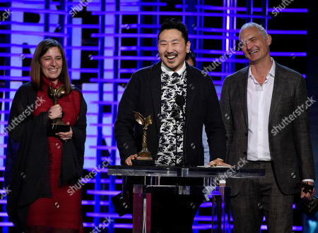 "Giulia Caruso, from left, Andrew Ahn, and David Ariniello accept the John Cassavetes award for ""Spa Night"" at the Film Independent Spirit Awards, in Santa Monica, Calif"