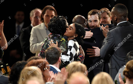 "Joi McMillon, left, embraces Janelle Monae and Nat Sanders, facing camera, embraces director Barry Jenkins in the audience after winning the award for best editing for ""Moonlight"" at the Film Independent Spirit Awards, in Santa Monica, Calif"
