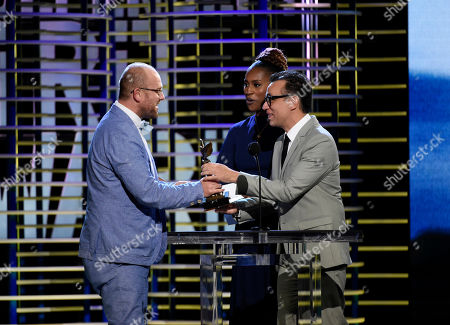 """James Laxton, left accepts the award for best cinematography for """"Moonlight"""" from Issa Rae, center, and Fred Armisen, right, at the Film Independent Spirit Awards, in Santa Monica, Calif"""