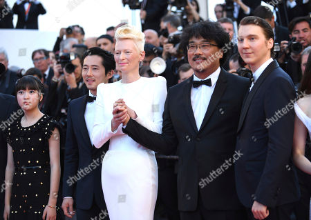 Actors Ahn Seo-Hyun, from left, Tilda Swinton, director Bong Joon-Ho and actor Paul Dano pose for photographers upon arrival at the screening of the film Okja at the 70th international film festival, Cannes, southern France