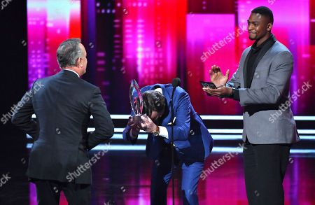 Tom Hanks, left, accepts the award for favorite dramatic movie actor from Bill Paxton, center, and Justin Cornwell at the People's Choice Awards at the Microsoft Theater, in Los Angeles