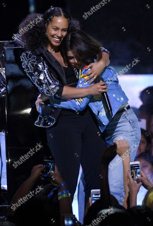 Stock Photo of Selena Gomez, right, hugs Alicia Keys at WE Day California at the Forum, in Inglewood, Calif