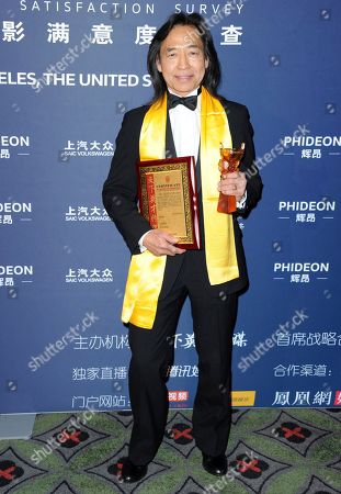 """Stock Photo of Jeff Imada, winner of the award for best global action choreography for """"Furious 7"""" poses in the press room at the 21st annual Huading Global Film Awards at The Theatre at Ace Hotel, in Los Angeles"""