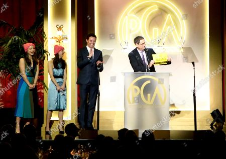 Tom Rothman, right, accepts the award for milestone award at the 28th Annual Producers Guild Awards at the Beverly Hilton, in Beverly Hills, Calif. Nora Rothman, from left, Elizabeth Rothman, and Hugh Jackman look on from left