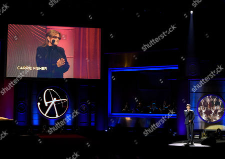"""Max Ehrich performs """"Hallelujah"""" on stage during an in memoriam tribute at the 44th annual Daytime Emmy Awards at the Pasadena Civic Center, in Pasadena, Calif. Carrie Fisher appears on-screen"""