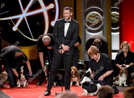 Brandon McMillan speaks on stage with the dogs of DaphneyLand Basset Rescue and their handlers at the 44th annual Daytime Emmy Awards at the Pasadena Civic Center, in Pasadena, Calif