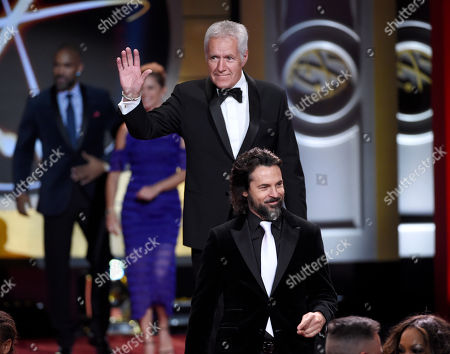 Alex Trebek, in back, and Jeffrey Vincent Parise walk out on stage at the 44th annual Daytime Emmy Awards at the Pasadena Civic Center, in Pasadena, Calif