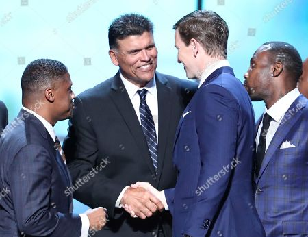 Former NFL players Warrick Dunn, from left, and Anthony Munoz, congratulate Eli Manning of the New York Giants with the Walter Payton NFL Man of the Year Award at the 6th annual NFL Honors at the Wortham Center, in Houston