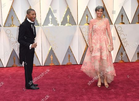 Pharrell Williams, left, and Mimi Valdes arrives at the Oscars, at the Dolby Theatre in Los Angeles