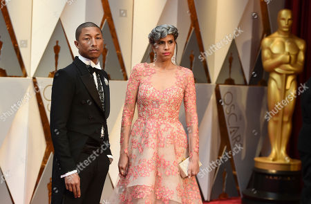 Pharrell Williams, left, and Mimi Valdes arrive at the Oscars, at the Dolby Theatre in Los Angeles