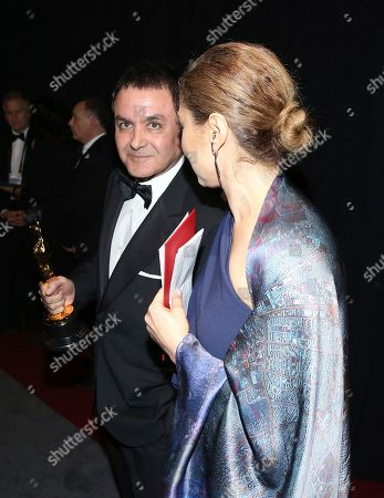 "Firouz Naderi, left, and Anousheh Ansari appear backstage with the award for best foreign language film for ""The Salesman"" at the Oscars, at the Dolby Theatre in Los Angeles"