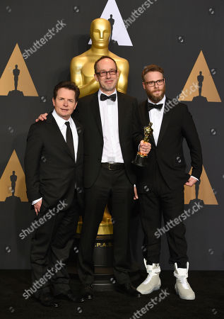 "John Gilbert, center, winner of the award for best film editing for ""Hacksaw Ridge,"" poses in the press room with Michael J. Fox, left, and Seth Rogen, right, at the Oscars, at the Dolby Theatre in Los Angeles"