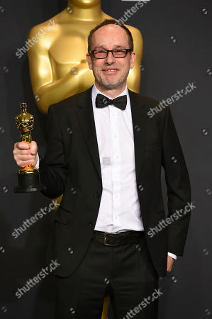 "John Gilbert poses in the press room with the award for best film editing for ""Hacksaw Ridge"" at the Oscars, at the Dolby Theatre in Los Angeles"
