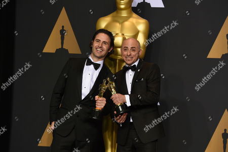 """Alan Barillaro, left, and Marc Sondheimer, winners of the award for best animated short film for """"Piper"""", pose in the press room at the Oscars, at the Dolby Theatre in Los Angeles"""