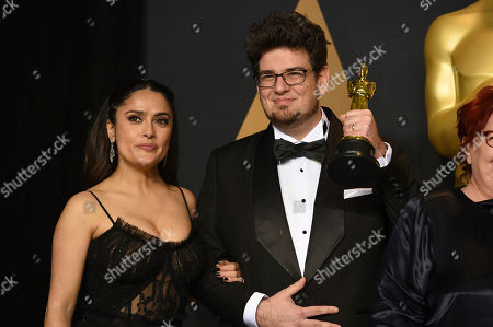 """Salma Hayek, left, and Kristof Deak, winner of the award for best live-action short film for """"Sing"""", pose in the press room at the Oscars, at the Dolby Theatre in Los Angeles"""