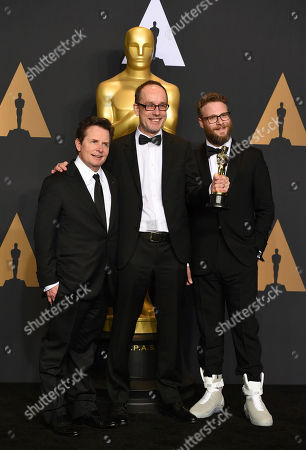 "John Gilbert, center, winner of the award for best film editing for ""Hacksaw Ridge"", poses in the press room with Michael J. Fox, left, and Seth Rogen, right, at the Oscars, at the Dolby Theatre in Los Angeles"