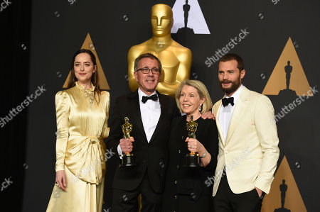 """David Wasco, second from left, and Sandy Reynolds-Wasco, winners of the award for best production design for """"La La Land"""", pose in the press room with Dakota Johnson, left, and Jamie Dornan, right, at the Oscars, at the Dolby Theatre in Los Angeles"""