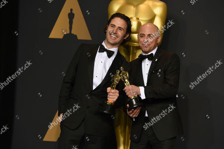"""Alan Barillaro, left, and Marc Sondheimer pose in the press room with the award for best animated short film for """"Piper"""" at the Oscars, at the Dolby Theatre in Los Angeles"""
