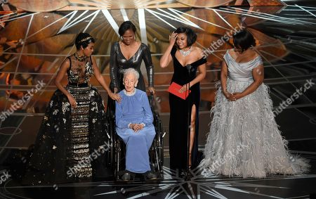 Janelle Monae, from left, Katherine Johnson, Taraji P. Henson, and Octavia Spencer present the award for best documentary feature at the Oscars, at the Dolby Theatre in Los Angeles