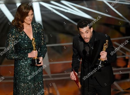 """Ezra Edelman, right, and Caroline Waterlow accept the award for best documentary feature for """"O.J.: Made in America"""" at the Oscars, at the Dolby Theatre in Los Angeles"""