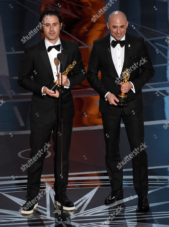 """Alan Barillaro, left, and Marc Sondheimer accept the award for best animated short film for """"Piper"""" at the Oscars, at the Dolby Theatre in Los Angeles"""