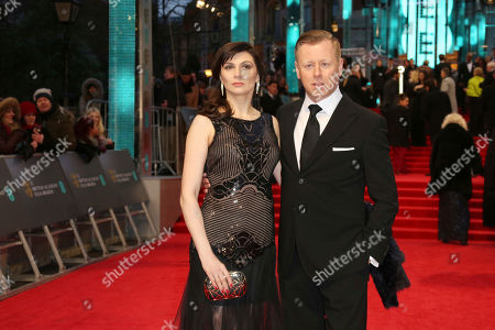 Stock Image of Composer Abel Korzeniowski, right, and his wife Mina Korzeniowski pose for photographers upon arrival at the British Academy Film Awards in London