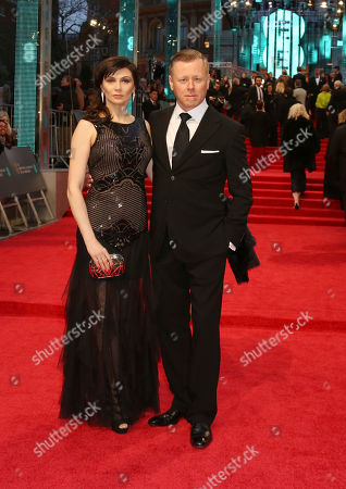 Composer Abel Korzeniowski, right, and his wife Mina Korzeniowski pose for photographers upon arrival at the British Academy Film Awards in London