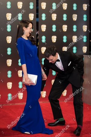 Olivia Bennett and Rupert Evans pose for photographers upon arrival at the BAFTA Film Awards, in London