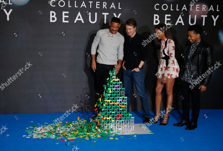 Actor Will Smith, left, knocks down the domino christmas tree as he poses with fellow actors from second left Ed Norton, Naomie Harris and Jacob Latimore during a photo call for the film 'Collateral Beauty' in London