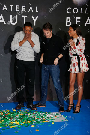 Actor Will Smith, left, knocks down the domino christmas tree as he poses with fellow actors from second left Ed Norton and Naomie Harris during a photo call for the film 'Collateral Beauty' in London