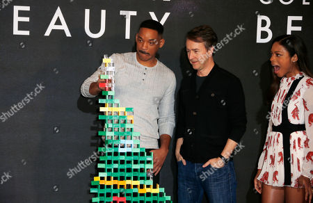 Actor Will Smith, left, begins to knock down the domino christmas tree as he poses with fellow actors Ed Norton, centre, and Naomie Harris during a photo call for the film 'Collateral Beauty' in London