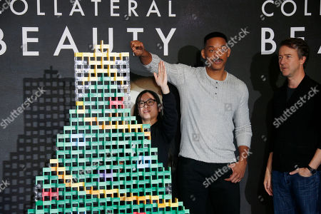 Domino artist Lily Hevesh, left, prevents actor Will Smith, centre, from touching the domino christmas tree as they pose with fellow actor Ed Norton during a photo call for the film 'Collateral Beauty' in London