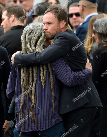 Jeff Ament, of Pearl Jam, hugs a guest at a funeral for Chris Cornell at the Hollywood Forever Cemetery, in Los Angeles