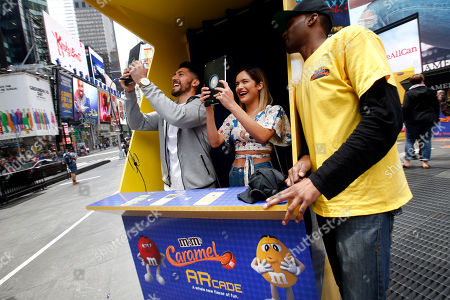 Stock Photo of Josh Levya and Chachi Gonzales celebrate the launch of new M&M'S Caramel at the M&M'S Arcade, an innovative augmented reality gaming experience in the heart of New York's Times Square