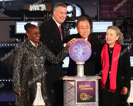 New York City Mayor Bill de Blasio, second from left, his wife Chirlane McCray, left, United Nations Secretary-General Ban Ki-moon, second from right, and his wife Yoo Soon-taek prepare to push the Waterford crystal button that begins the 60-second countdown to 2017 during a New Year's Eve celebration in New York's Times Square